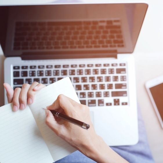 a laptop and a hand writing on a notebook in an seo writing agency