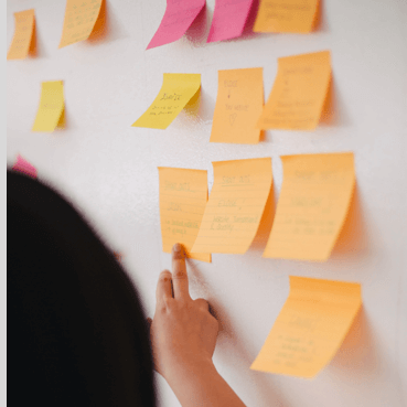 a woman reading post-it notes on the wall