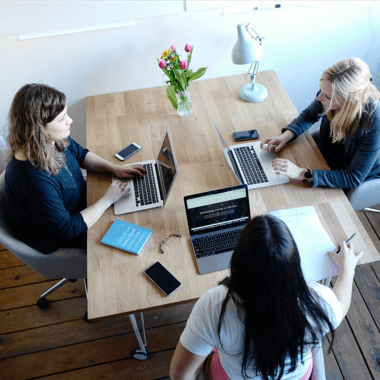 3 women in an seo agency, sitting in front of their laptops, working